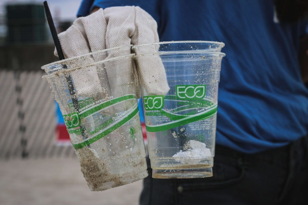 gloved hand holding two bioplastic cups