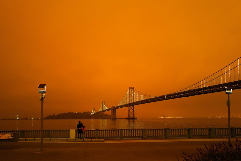 View of Golden Gate Bridge with blood orange sky, couple facing away looking.