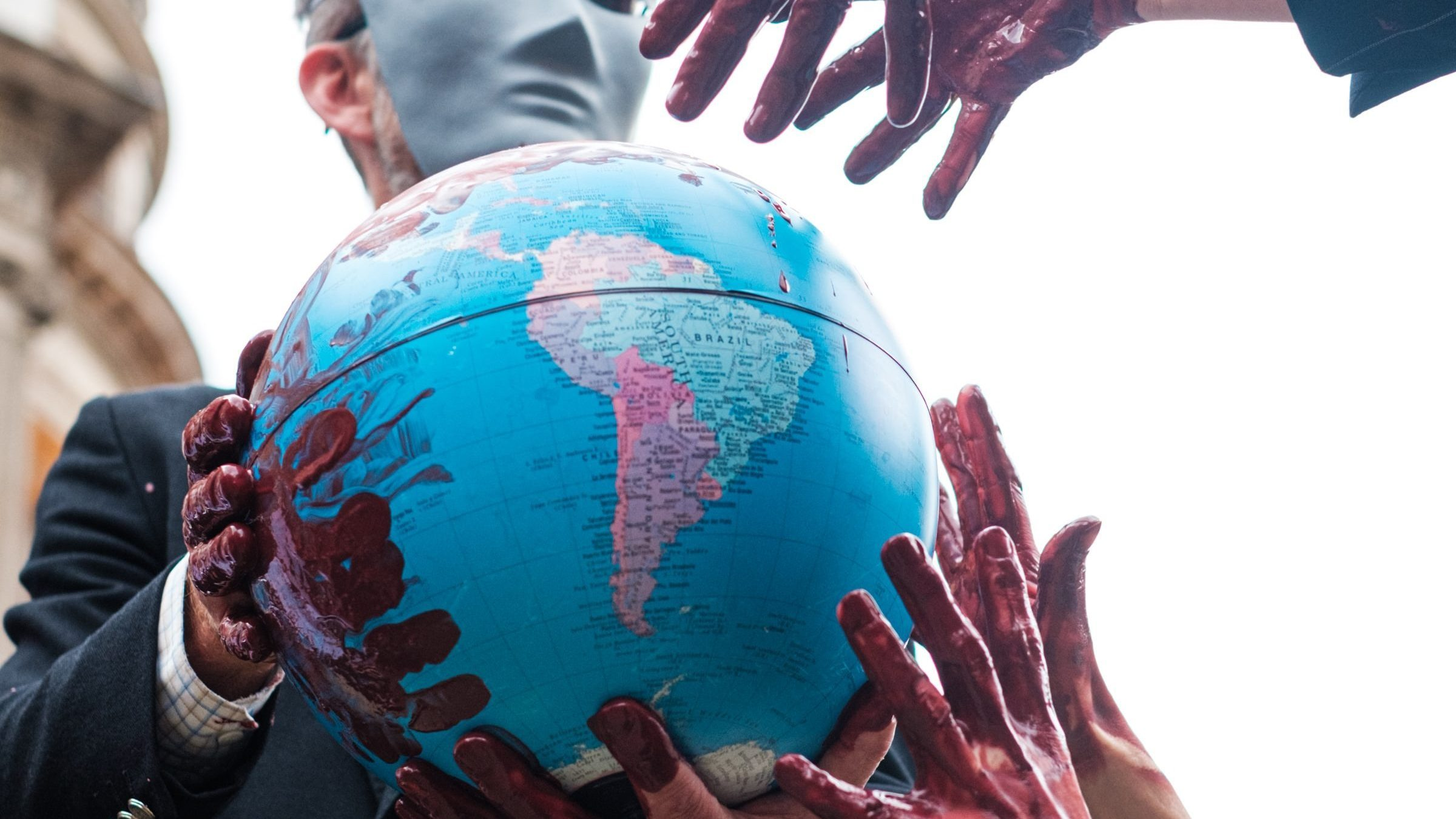 bloody hands reaching toward/ on globe of earth, masked man