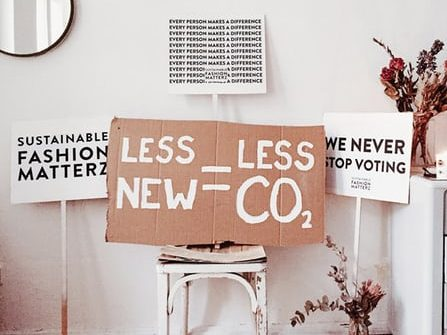 signs on/ near chair - less new = less co2, sustainable fashion matterz, we never stop voting