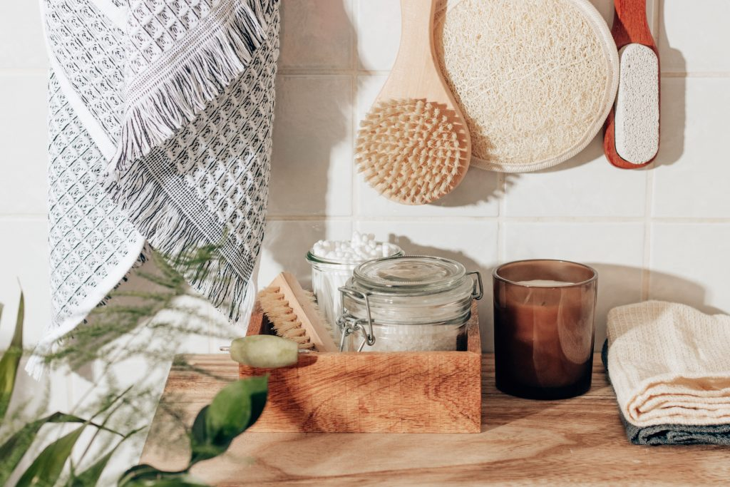 sustainable bathroom items - washcloths, loofahs, glass jars of q tips, candle