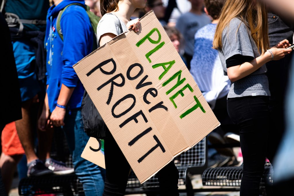 "woman at protest holding cardboard sign stating, ""PLANET over PROFIT"""