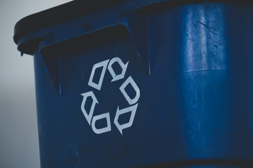 close-up of blue bin with white recycling arrows triangle