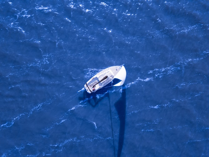 overhead view of sailboat on blue water
